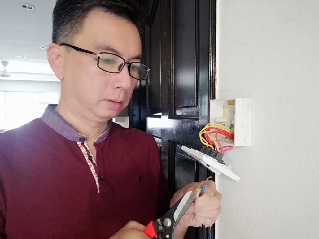 Residential Electrician fixing electrical socket at HDB flat