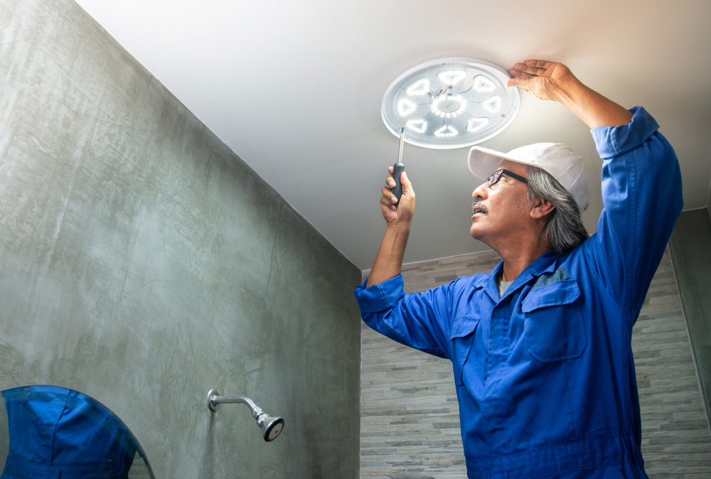 Asian Electrician Installs Led Replacement Lamp